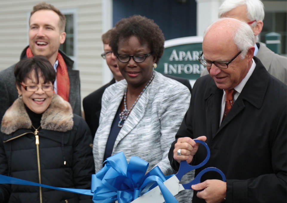 Elderly gentleman in a black suit cutting a blue ribbon at a ribbon cutting ceremony
