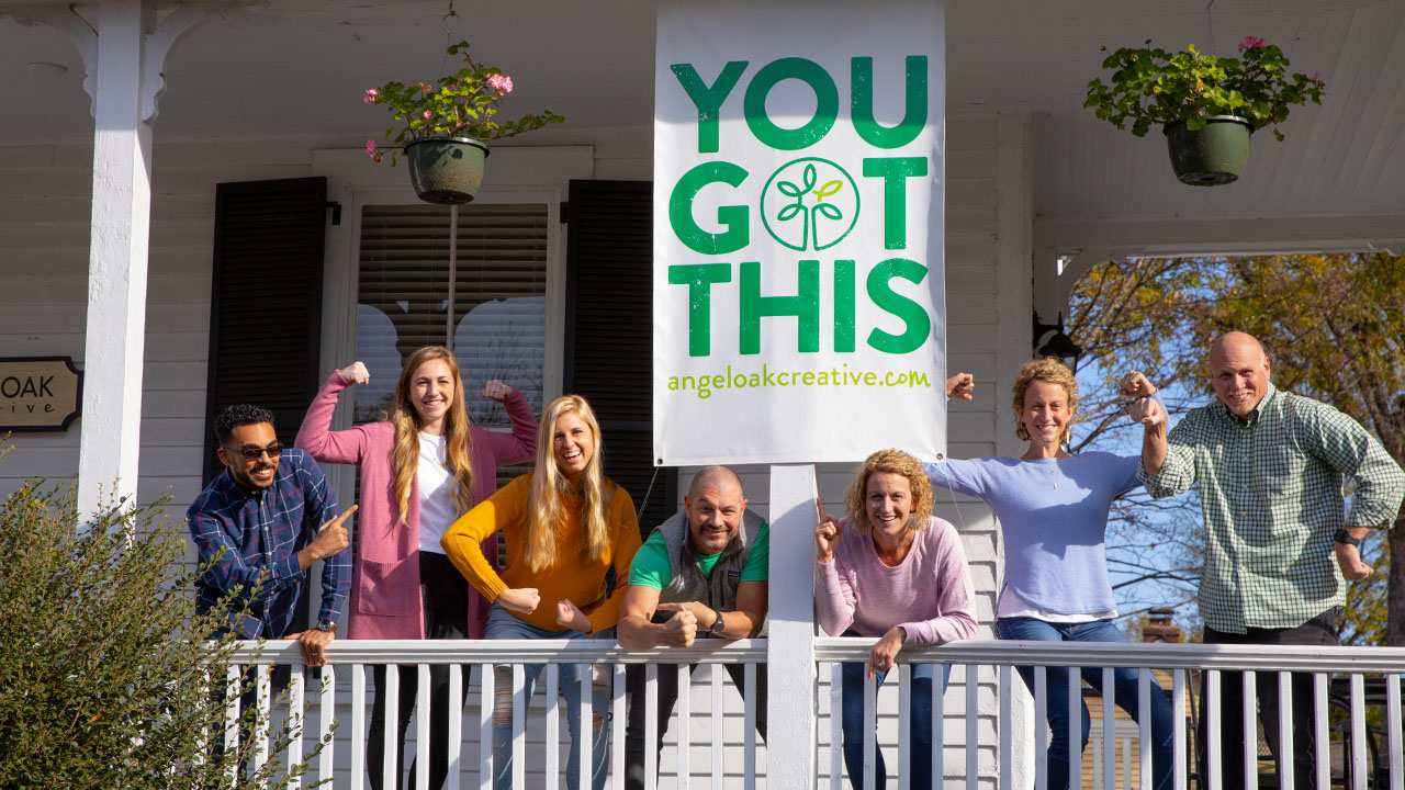 7 Angel Oak Creative employees standing together on a porch