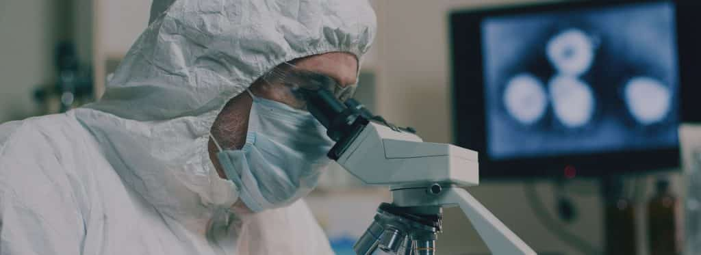 Surgeon with personal protective equipment looking through a microscope